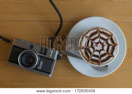 hot coffee and retro camera with star chocolate whipped-cream and coffee bean happy sign on wooden table in coffee shop