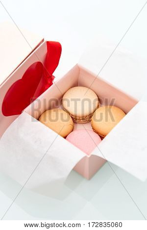 4 colorful macaroons wrapped in the Valentine's Day themed pink box with red heart and bow on top of the box.