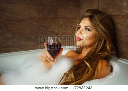 Young cute girl drinking red wine in bath with foam. She relaxes after a hard day. Girl dreams.
