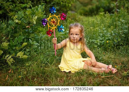 Cute little girl holding a pinwheel. She sits on the lawn. A walk in the summer park. Summer vacation. Outdoor Activities.