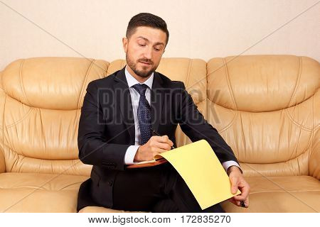 successful business man with business documents sitting on a leather sofa