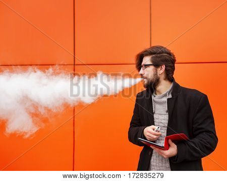 Young hipster man with a beard and glasses smokes an electronic cigarette. He holds a tablet pc. Youth fashion. Delicious pairs. A man and a social network.