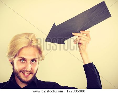Man Holding Black Arrow Pointing At Himself