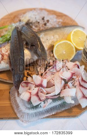 Sliced frozen raw fish from whitefish species - white salmon, whitefish, decorated with whole fishes, ice, lemon and greens. Siberian cuisine