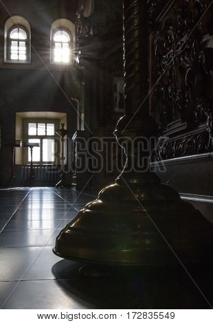 Inside Christian Church - candle holder in orthodox church at sunny day, silhouette, vertical