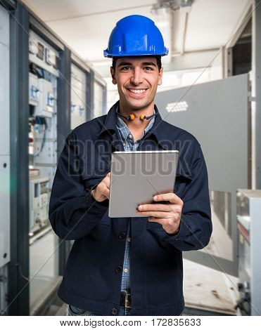 Electrician using a tablet in a cabinet