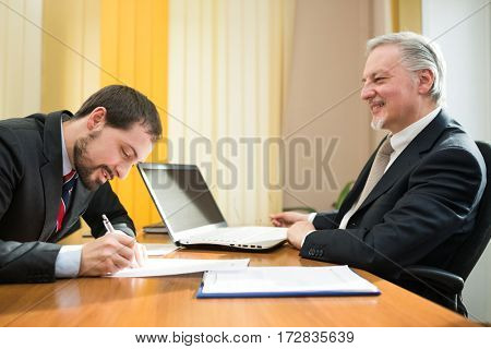 Happy businessman signing a deal