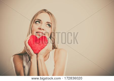 Valentines day love and relationships concept. Blonde long hair young woman holding red heart love symbol studio shot