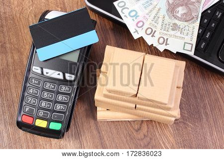 Payment Terminal With Credit Card, Polish Money, Laptop And Wrapped Boxes On Wooden Pallet