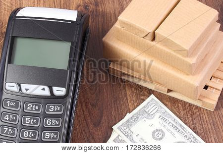 Payment Terminal, Currencies Dollar And Wrapped Boxes On Wooden Pallet