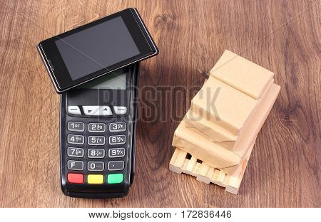 Payment Terminal With Mobile Phone With Nfc Technology And Wrapped Boxes On Wooden Pallet