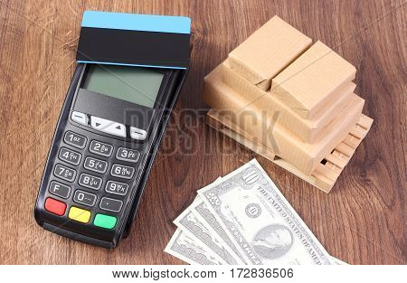 Payment Terminal With Credit Card, Currencies Dollar And Wrapped Boxes On Wooden Pallet