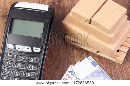 Payment Terminal, Currencies Euro And Wrapped Boxes On Wooden Pallet