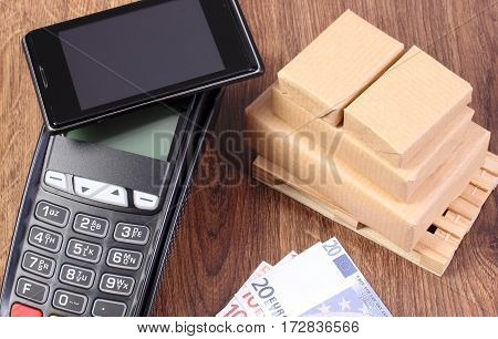 Payment Terminal With Mobile Phone With Nfc Technology, Currencies Euro And Wrapped Boxes On Wooden