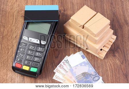 Payment Terminal With Credit Card, Currencies Euro And Wrapped Boxes On Wooden Pallet