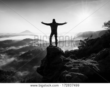 Man Silhouette Climbing High On Cliff. Hiker Climbed Up To Peak Enjoy View.