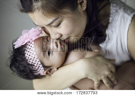 A beautiful asian mother holding her newborn baby