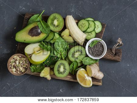 Detox green vegetables and fruits on a wooden board. Concept of a healthy diet food. Smoothie ingredients.Top view