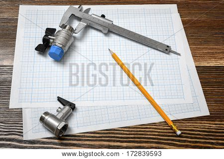 A large vernier scale lying on cross section paper with two ball valves and a pencil lying beside on wooden table background. Engineering systems. Repair works. Plumbing.