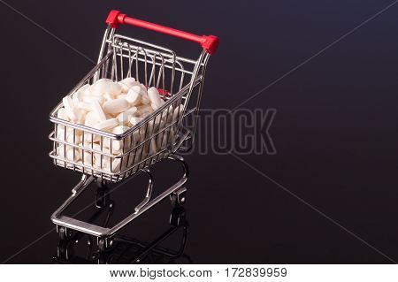 Shopping cart filled with medicine isolated on black glossy background