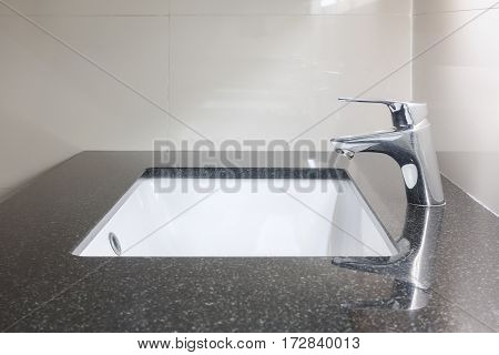 Under Counter Lavatory With Black Granite Top And Faucet
