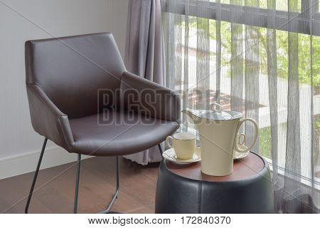 China Ware Tea Set On Table Next To Black Leather Chair In The Corner Of Living Room