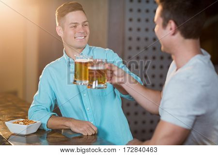 Two smiling male friends toasting beer mugs at counter in bar