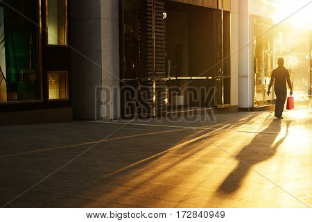 A shopper walking past a store window at sunrise in the shopping street .