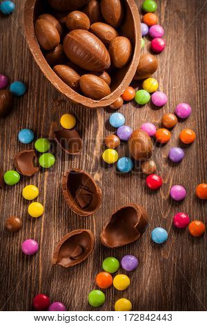 Assorted chocolate eggs for Easter on wooden background