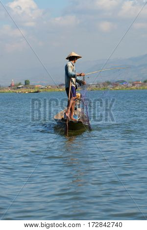 INLE LAKE, MYANMAR - DECEMBER 26, 2016: The fisherman by the wooden boat untangles a fishing net. Lake Inle, Myanmar