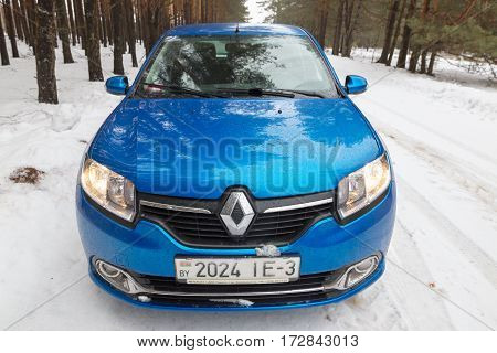Gomel, Belarus - February 21, 2017: Car Renault - Logan In The Winter Forest With Headlights.