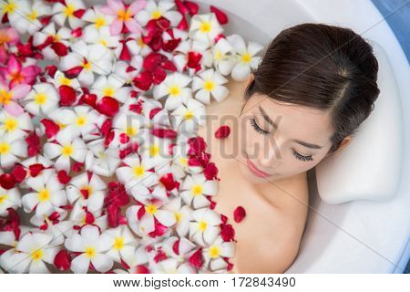 Milk and flower shawer Spa Relaxation. Woman Body Care. Beautiful Sexy Asian Blonde Girl In Bikini Lying In Flower Bath In Resort Day Spa Salon. Beauty Treatment Skin Care Therapy. Wellness. Healthy Lifestyle Concept