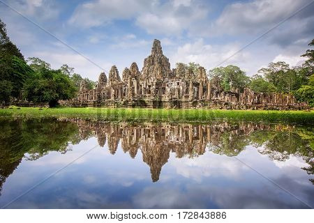 Main view of ancient Bayon temple in Angkor Thom in evening sun. Mysterious Angkor Thom nestled among rainforest in Siem Reap Cambodia. Enigmatic Angkor Thom is a popular tourist attraction.