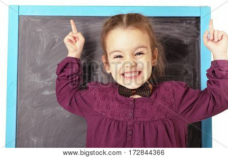 Cute little emotional girl standing near blackboard and happy smiling. Beautiful schoolgirl. Smart pupil girl in classroom. Have idea concept, image toned.