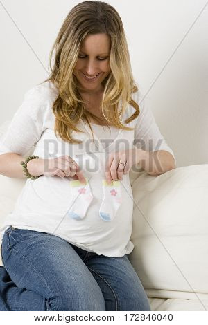 Pregnant woman sitting on the sofa smiling.