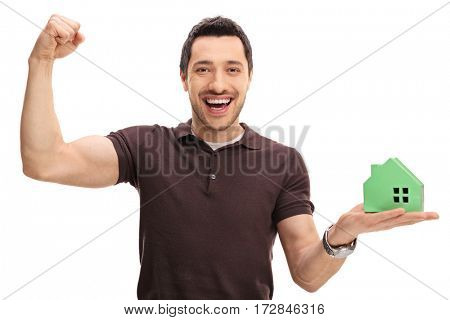 Cheerful guy holding a model house and gesturing happiness isolated on white background