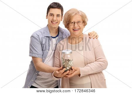 Young man and a mature woman holding a jar with money isolated on white background