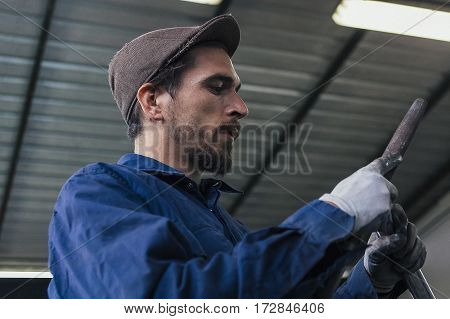 Side view of bearded worker holding two iron bars
