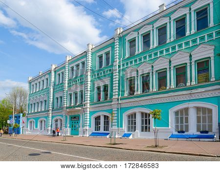 GOMEL BELARUS - MAY 1 2016: Unidentified people walk down street near building of JSC Polespechat (previously - building of City Duma built in eighties of XIX century by architect E.K.Torlin had 2 floors third floor overbuilt in 1935)