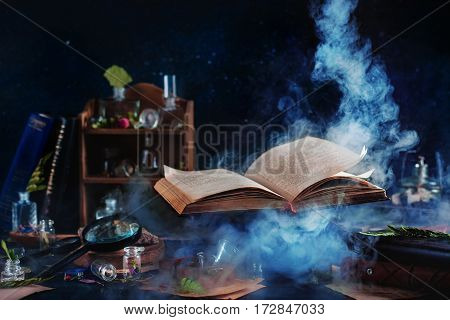 Still life with levitating book of spells, jars and bottles on a dark background with rising mystic smoke