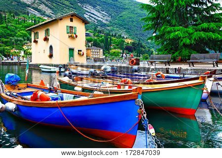 Pictorial scenery with boats in beautiful lake Lago di Garda. Torbole village