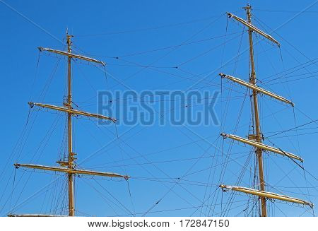 Masts and rigging of a sailing ship against blue sky