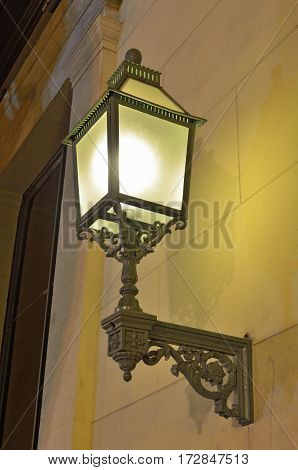 The lantern hanging on the walllights the street to passers-by.