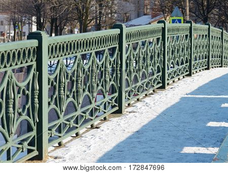 The iron railing of the bridge painted green.