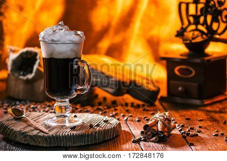 Irish coffee served on rustic wood. Cinnamon sticks, grinder and coffee beans . Fire light on the background