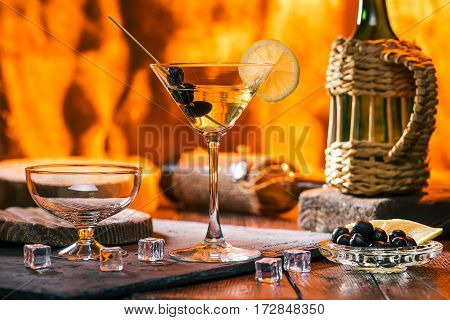 Martini cocktail and empty glass for ice-cream over fire lighting background