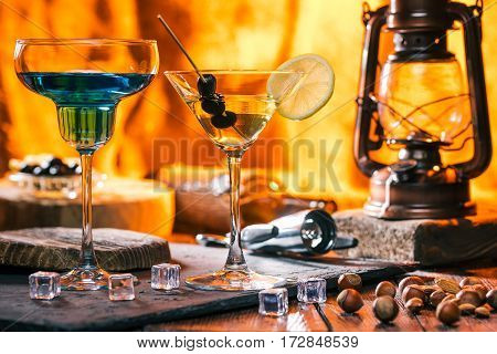 Various cocktails in margarita and martini glasses. Nuts on bar counter over fireplace light