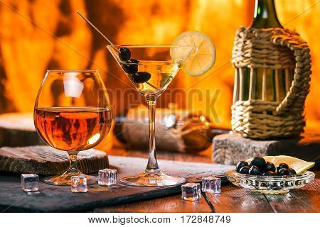 Martini in cocktail glass. Brandy in snifter. Olives and lemon. Bar counter next to fireplace