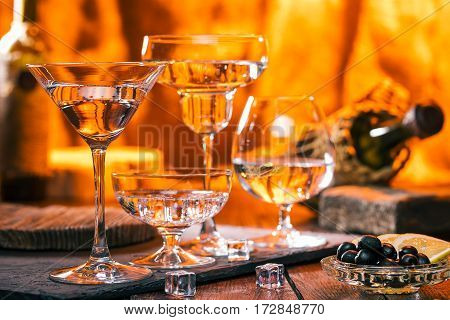 Various glasses with sparkling cocktails. Wine and fireplace on the background