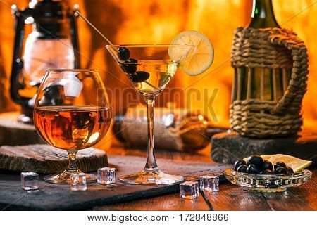 Martini cocktail and brandy on bar counter next to fireplace